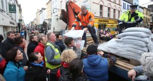 People collect sand bags from Cork County Council workers on Oliver Plunkett Street as they prepare for flooding this evening in Cork. Photograph: Niall Carson/PA