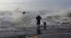 A screen grab of the YouTube clip showing a woman running from a large wave in Tramore, Co Waterford.