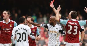 West Ham's Andy Carroll (left) gets a red card after a challenge with Swansea's Chico Flores. Photograph: Sean Dempsey/PA