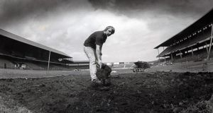 General view of a groundskeeper repairing the damage done to the pitch after the U2 concert which caused the postponement of the Leinster hurling final. Photograph: Inpho