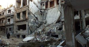 A man walks along a street lined with damaged buildings in the besieged area of Homs. Photograph: Yazan Homsy/Reuters.