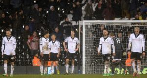 Fulham players stand dejected after Sheffield United scored what turned out to be  a late winner in their FA Cup Fourth Round replay at Craven Cottage. Already out of both cups, the London side also look like prime candidates for Premier League relegation. Photograph:  Andrew Matthews/PA Wire