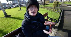 Tomas (43), from Slovakia, who has lived homeless in Dublin for the past four years, photographed in Wolfe Tone Quay park with a picture of his son. Photograph: Brenda Fitzsimons