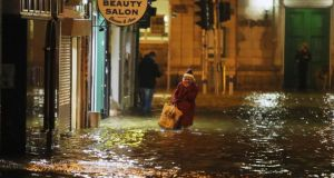A woman walks through flood water in Cork city last week. The city is considering a plan to spend up to €100 million on measures including erecting up to 12km of protective barriers on the city's quays. Photograph: PA Wire