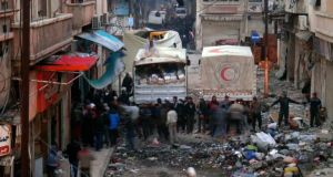 Syrian Arab Red Crescent trucks arrive  in the besieged neighbourhoods of Homs to supply humanitarian aid yesterday. Photograph: Reuters