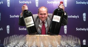 Robert Sleigh, head of Asia wine sales for Sotheby's, poses for a photograph with an imperial of Chateau Lafite 2000
