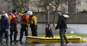 Residents use a boat to navigate flood waters after a flash flood on the Lee Estate in Limerick City.