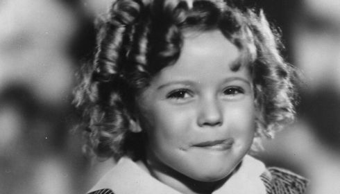 Shirley Temple pictured enjoying a soft drink with an impish grin on her face.  Photograph: Hulton Archive/Getty Images