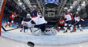 Canada's Meghan Agosta-Marciano (left) scores what turns out to be the game-winning goal past Team USA's goalie Jessie Vetter during the third period of their women's ice hockey game at the 2014 Sochi Winter Olympics. Photograph:  Matt Slocum/Reuters