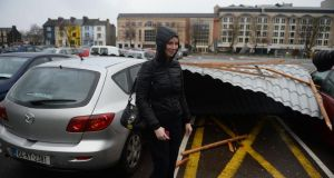 Charlotte Kelleher stands by her damaged car in Tralee, Co Kerry,   after powerful winds blew off part of  the  roof of  the Brandon Hotel  into a car  park. Photograph: Domnick Walsh/Eye Focus