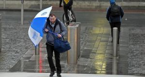 Battling with rain and high winds on the Sean O'Casey Bridge  over the River Liffey in Dublin yesterday. Photograph: Eric Luke/The Irish Times