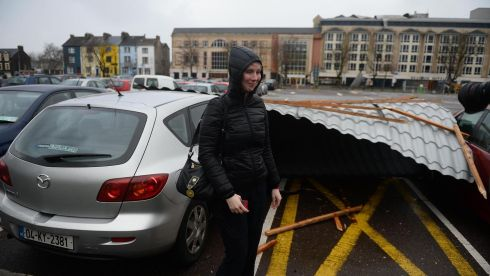 Charlotte Kelliher stands by her damaged car in Tralee. A significant part  part of the Brandon Hotel roof  in Tralee town centre was blown off by powerful winds, landing on cars in the car park below. Photograph: Domnick Walsh / Eye Focus LTD