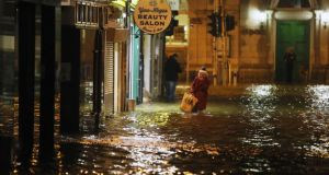 A woman walks through flood water in Cork city recently. Photograph: Niall Carson/PA