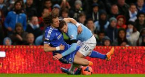 Manchester City's Edin Dzeko battles for the ball with David Luiz at the Etihad Stadium. Photograph:  Dave Thompson/PA Wire.