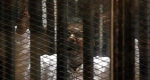 Former  Egyptian president Mohammed Morsi pictured inside the  cage in the  makeshift courtroom inside a police academy in Cairo where his trial is being held.  Photograph: Almasry Alyoum/EPA