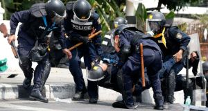 Thai police officers assist a colleague after an explosion during clashes with anti-government protesters near Government House in Bangkok today. Photograph: Athit Perawongmetha/Reuters.