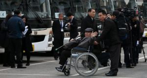 South Korean Jang Chun (82) waves as he leaves for North Korea's Mount Kumgang resort to meet his family members. Photograph:  Yonhapp/EPA.