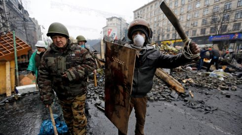 "Anti-government protesters react after clashes with riot police in the Independence Square in Kiev, February 20th. Ukrainian protesters hurling petrol bombs and paving stones drove riot police from the central square in Kiev despite a ""truce"" that  embattled Ukrainian president Viktor Yanukovich said he had agreed with opposition leaders.  Photograph: Reuters/Yannis Behrakis"