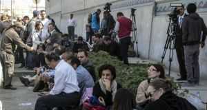 Foreign and local journalists wait before the start of the trial of the journalists accused of allegedly supporting a terrorist group and spreading false information, outside Torah prison, southern Cairo, Photograph: Mohamed Kamal/EPA