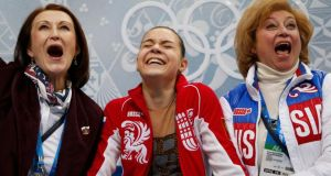 "Russia's Adelina Sotnikova (centre) reacts with her choreographer Irina Tagaeva (left) and her coach Elena Buyanova (right) ecstatic in the ""kiss and cry"" area after seeing her results   in the figure skating final at the Sochi 2014 Winter Olympics. Photograph:  Lucy Nicholson/Reuters"