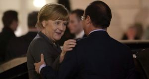 Chancellor Angela Merkel with French president François Hollande as she leaves the Élysée Palace.  Photograph: Reuters