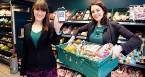 Aoibheann O'Brien and Iseult Ward, co-founders of FoodCloud, a company trying to minimise food waste by supermarkets and other retailers. Aoibheann is pictured with a donation basket from Tesco in Ringsend, Dublin, while Iseult displays the company's phone app. photograph: dave meehan