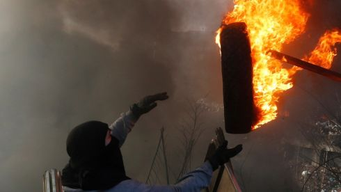 An anti-government protester throws a burning tyre at a barricade in Kiev. Photograph: Baz Ratner/Reuters
