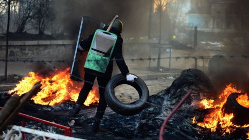 Protester adds more tyres to the fire on the front line at the barricades in Kiev. Photograph: Jeff J Mitchell/Getty Images