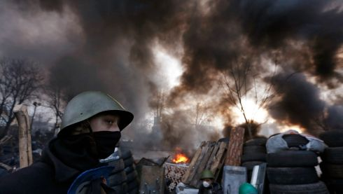 A protester keeps watch as fire and black smoke surround the barricades. Photograph: Baz Ratner/ Reuters