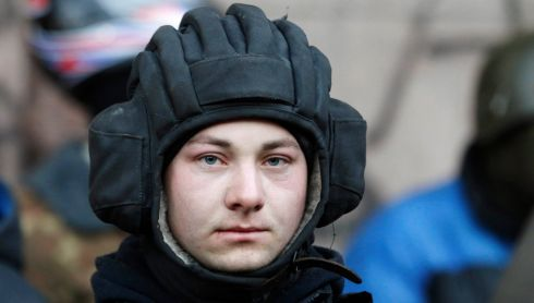 A protester keeps watch by the barricades in Kiev. Photograph: Baz Ratner/Reuters