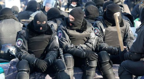 Riot police sit and wait near parliament in Kiev. Photograph: Olga Yakimovich/Reuters