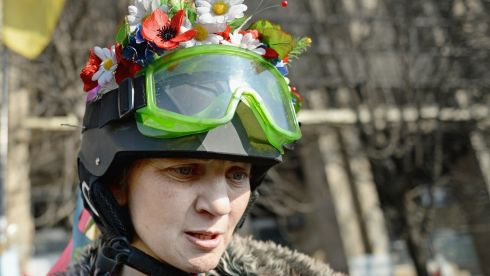 An anti-government demonstrator wears flowers in her helmet. Photograph: Jeff J Mitchell/Getty Images