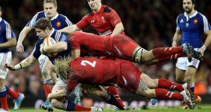 Wales' Richard Hibbard and Taulupe Faletau tackle Pascal Pape of France. Photograph: James Crombie/Inpho