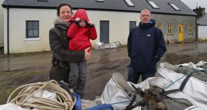 Céline and Ronan Coyne and their son Cormac (4) at their house which was hit by waves at East End village on Inishbofin after the pier was destroyed. Photograph: Joe O'Shaughnessy.