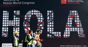 Workers walk past a Mobile World Congress banner in Barcelona. The GSMA Mobile World Congress will take place this week. Photograph: Reuters