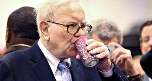 Warren Buffett, chief executive officer of Berkshire Hathaway, drinks a Cherry Coca-Cola as he tours the exhibition floor prior to the Berkshire Hathaway annual meeting in Omaha, Nebraska in 2010. In this year's annual letter to shareholders, the billionaire investor has urged investors to treat their equity holdings like real estate purchases, focusing on the potential for profits over time rather than short-term price fluctuations. Photograph: Daniel Acker/Bloomberg