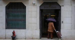 A woman enters the Bank of Portugal in Lisbon. The latest troika review of the Portuguese programme said that the programme was on track. Photograph:Rafael Marchante/Reuters