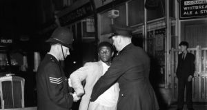 Police search a black youth in Notting Hill during race riots in 1958, subject of Laura Wilson's The Riot. Photograph: Knoote/Getty Images