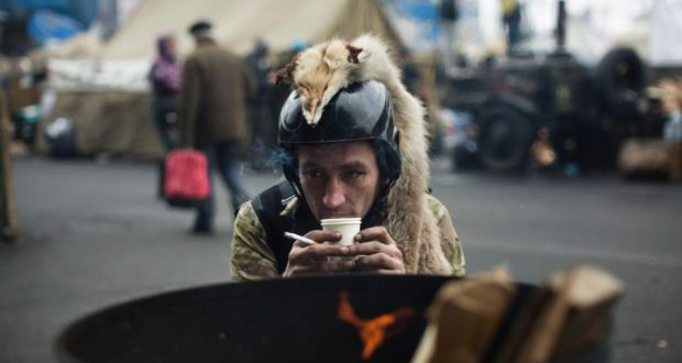 A member of a civilian defence unit warms up by a fire at Independence Square in Kiev today. Photograph: Uriel Sinai/The New York Times