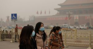 Chinese tourists wearing  face masks at Tiananmen Square, Beijing, during severe pollution today. Photograph: Lintao Zhang/Getty Images