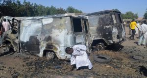 A boy searches the ground next to a burnt-out vehicle, caused by an attack from Boko Haram militants, in Bama, Borno State, on February 20th, 2014. Photograph: Reuters