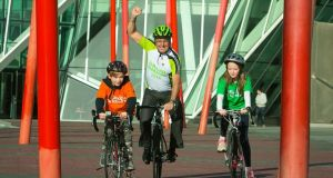 Tour De France winner Stephen Roche with Jack Ryan (10) (left)  from Rolestown and  Lucy Madden (10) from Mount  Merrion at Grand Canal Square, Dublin.  Roche has been named as the Grand Marshal for this year's St Patrick's Day parade.  Photograph: Collins
