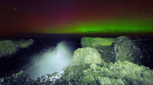 The Aurora Borealis or Northern Lights in full glory at Elephant Rock, Ballintoy, Co Antrim, with waves crashing in in the foreground. Photograph: Stephen Wallace/Hibernia Landscapes/@Hiberniaphoto