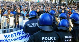 Police look on as demonstrators outside Cyprus's parliament protest plans by the government to sell off state-owned enterprises. Photograph: Andreas Manolis/Reuters