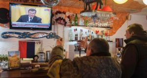 Kiev residents react as they watch a television broadcast of ousted Ukrainian president Viktor Yanukovich's news conference yesterday.  Photograph: Reuters/Alex Kuzmin