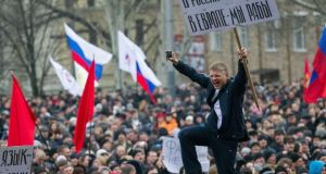 "Pro-Russian protesters with Russian flags take part in a rally in central Donetsk. The Crimea region has a majority ethnic Russian population. The banner reads, ""In Russia, we have brothers, In Europe, we are slaves"". Photograph: Reuters"