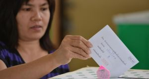 A voter castes a ballot at a polling station during re-run voting in Thailand's general election today in Samut Sakhon Town, Thailand. The poll re-run was held in five provinces where anti-government protesters disrupted general election voting in the previous month. Photograph: Rufus Cox/Getty Images