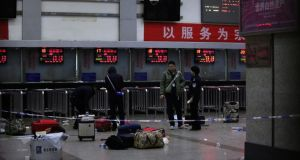 Police at the ticket office at Kunming railway station in China's Yunnan province after a group of armed men attacked people on Saturday evening. Photograph: Reuters