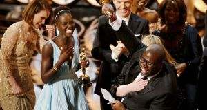 Director and producer Steve McQueen (R) celebrates after accepting the Oscar for best picture for his film '12 Years a Slave', with actress Lupita Nyong'o (L), at the 86th Academy Awards . Photograph: Lucy Nicholson/Reuters