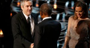 Alfonso Cuaron (L) accepts the best director Oscar for Gravity from presenters Angelina Jolie (R) and Sidney Poitier. Photograph: Lucy Nicholson/Reuters